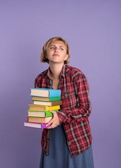 不機嫌な若いスラブ学生の女の子が本を持ち、横を見る