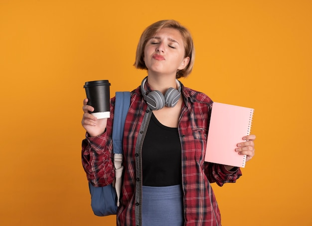 배낭을 착용하는 헤드폰으로 불쾌한 젊은 슬라브 학생 소녀는 노트북과 종이 컵을 보유하고 있습니다.