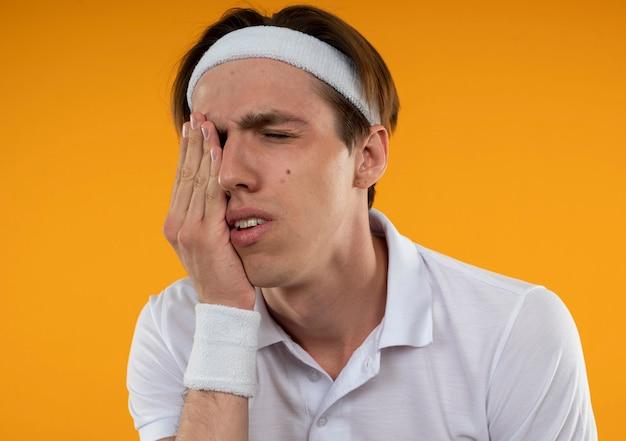 Giovane ragazzo sportivo dispiaciuto con gli occhi chiusi che indossa la fascia e il braccialetto mettendo la mano sull'occhio isolato sulla parete arancione
