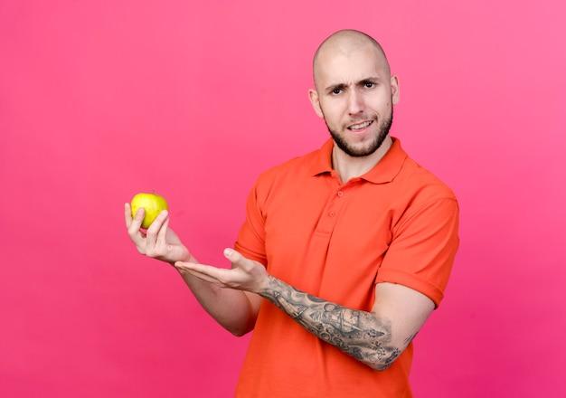 Giovane uomo sportivo dispiaciuto che tiene e punti con la mano alla mela isolata sulla parete rosa
