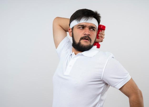 복사 공간이 흰 벽에 고립 된 아령으로 운동하는 머리띠와 팔찌를 착용하는 측면을보고 불쾌한 젊은 스포티 한 남자