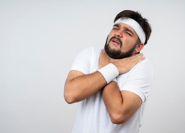 Il giovane sportivo dispiaciuto che guarda al lato che indossa la fascia e il braccialetto ha afferrato la gola isolata sulla parete bianca