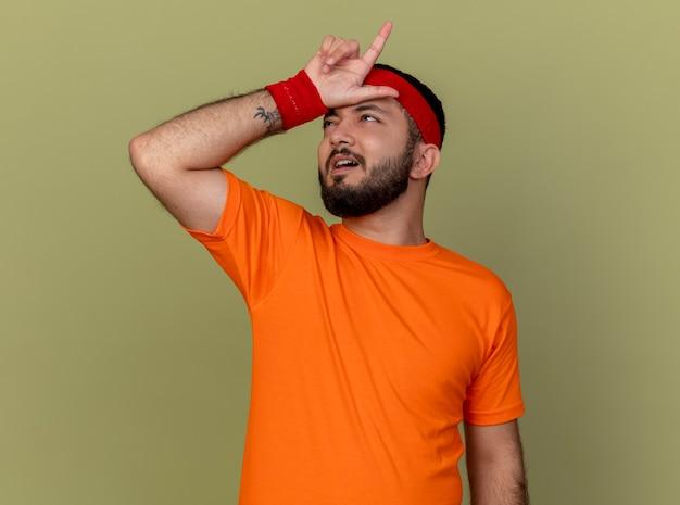 Недовольный молодой спортивный мужчина смотрит вверх с повязкой на голову и браслетом, показывая жест неудачника, изолированный на оливково-зеленом фоне