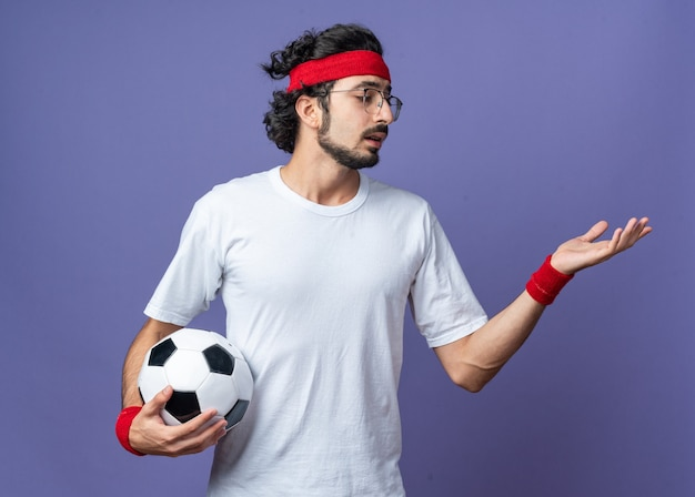 Unpleased young sporty man wearing headband with wristband holding ball holding out hand at side