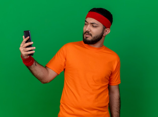 Unpleased young sporty man wearing headband and wristband holding and looking at phone isolated on green background