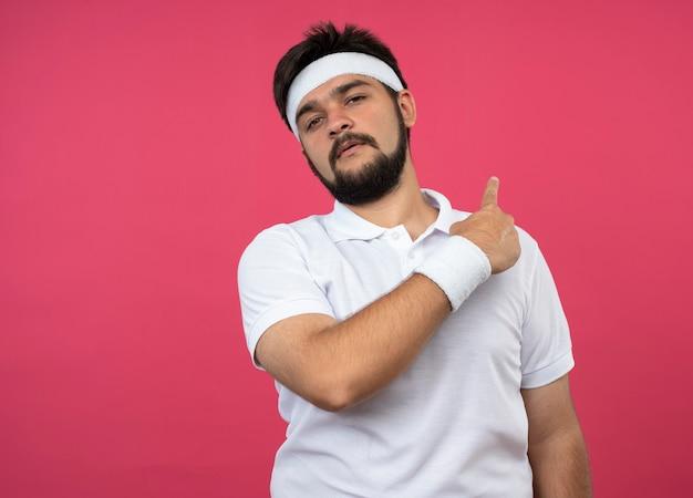 Il giovane sportivo dispiaciuto che indossa la fascia e il braccialetto indica dietro isolato sulla parete rosa con lo spazio della copia