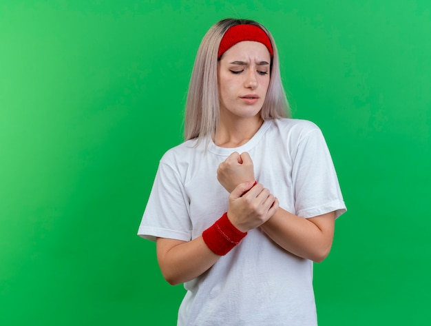 머리띠와 팔찌를 착용하는 중괄호가있는 불쾌한 젊은 스포티 한 여자가 녹색 벽에 고립 된 손을 잡고 있습니다.