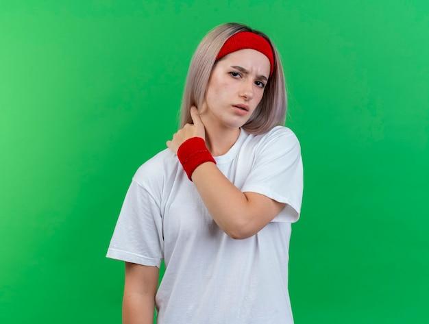 머리띠와 팔찌를 착용하는 중괄호가있는 불쾌한 젊은 스포티 한 여자가 녹색 벽에 고립 된 목에 손을 넣습니다.