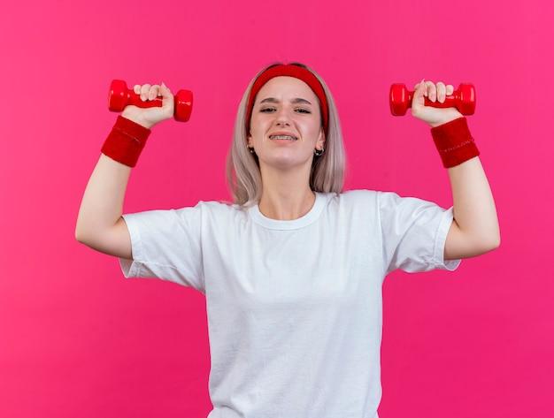La giovane donna sportiva dispiaciuta con le parentesi graffe che indossa la fascia e i braccialetti sta con le mani alzate che tengono i manubri isolati sulla parete rosa