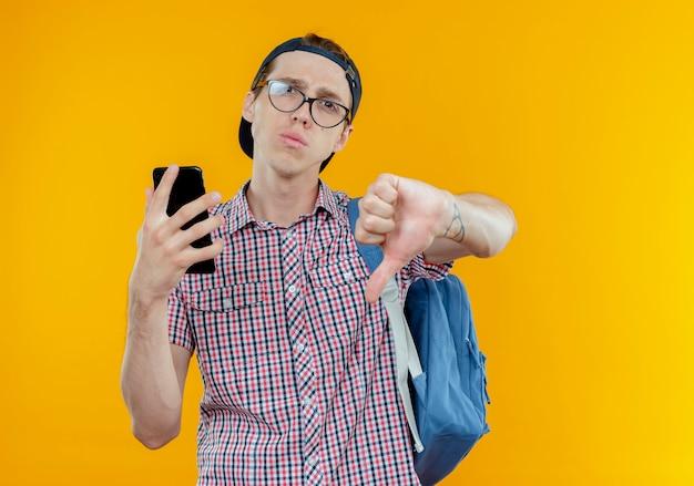 バックバッグとメガネとキャップを身に着けている不機嫌な若い学生の男の子は、白で彼の親指を下に電話を保持します