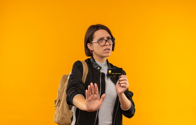 Недовольная молодая студентка в очках и спине с сумкой, держащей кредитную карту, жестикулируя, остановившись на оранжевом фоне с копией пространства