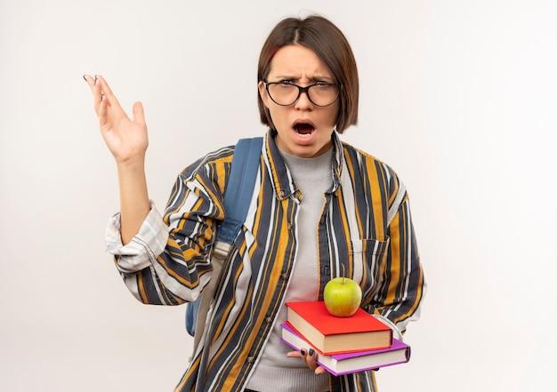 Недовольная молодая студентка в очках и спине, поднимающая сумку, рука, держащая книги с яблоком на ней, изолирована на белом фоне с копией пространства