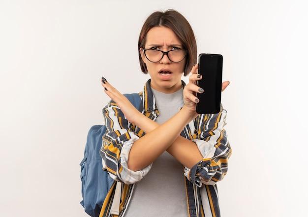 Недовольная молодая студентка в очках и задней сумке, показывающая мобильный телефон, не делающий жестов сбоку, изолирована на белом фоне с копией пространства