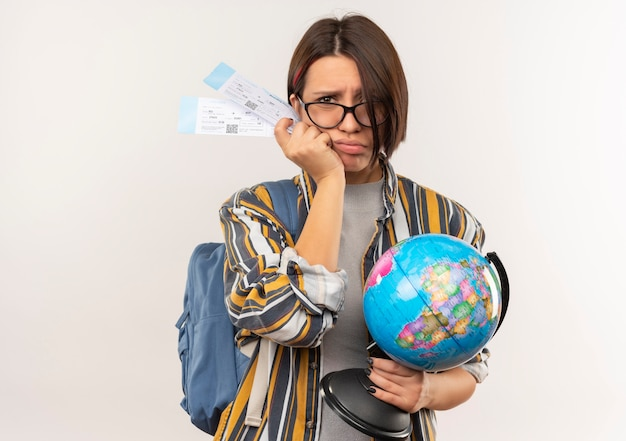 Unpleased young student girl wearing glasses and back bag holding airplane tickets and globe isolated on white background with copy space