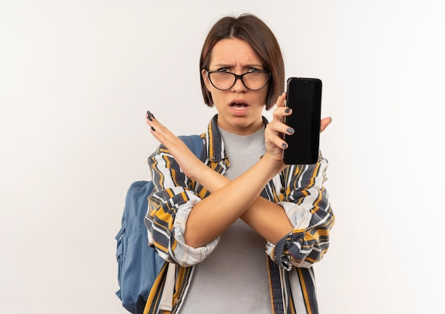 Ragazza giovane studente dispiaciuto con gli occhiali e borsa posteriore che mostra il telefono cellulare non facendo alcun gesto a lato isolato su priorità bassa bianca con lo spazio della copia