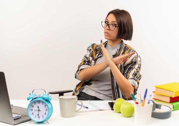 흰색 배경에 고립 몸짓 대학 도구로 책상에 앉아 안경을 쓰고 불쾌한 젊은 학생 소녀