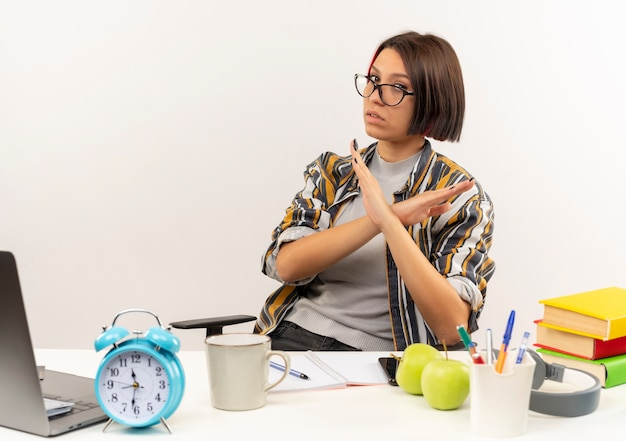 Unpleased young student girl wearing glasses sitting at desk with university tools gesturing no isolated on white background