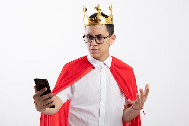 眼鏡と王冠を身に着けている赤いマントの不機嫌な若いスーパーヒーローの少年は、白い背景で隔離の空気中に手を保持している携帯電話を保持し、見ています