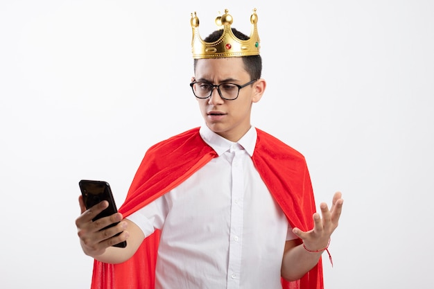 Unpleased young superhero boy in red cape wearing glasses and crown holding and looking at mobile phone keeping hand in air isolated on white background