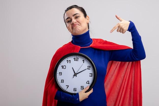 Ragazza giovane supereroe dispiaciuto che tiene e punti all'orologio di parete isolato su bianco