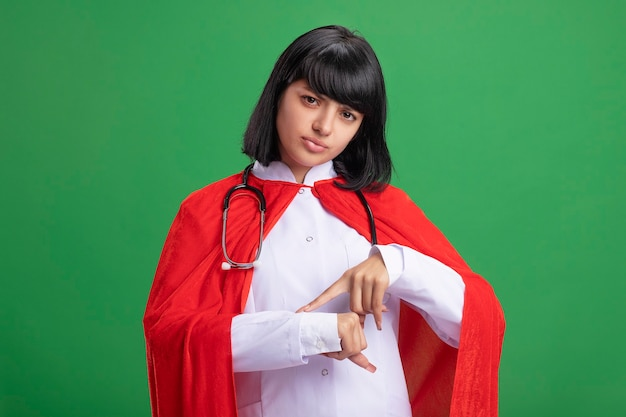 Недовольная молодая девушка-супергерой в стетоскопе с медицинским халатом и плащом, показывающая жест наручных часов, изолированный на зеленой стене