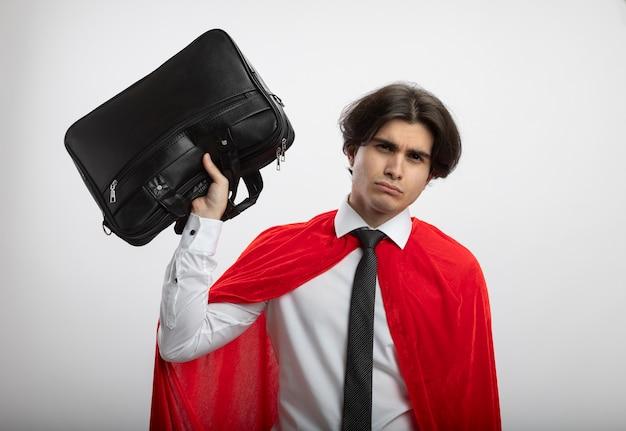 흰색 배경에 고립 된 핸드백을 올리는 넥타이 착용 카메라를보고 불쾌한 젊은 슈퍼 히어로 남자