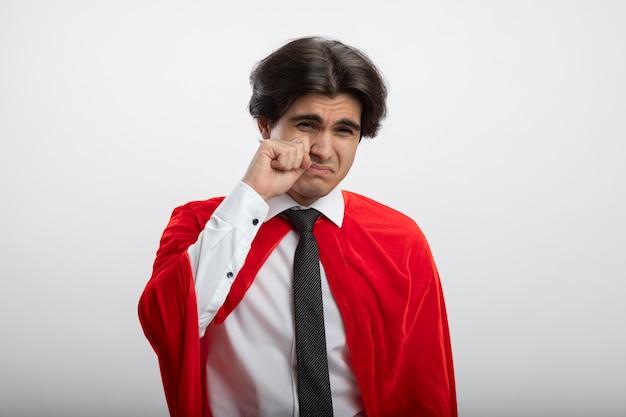 Недовольный молодой супергерой смотрит в камеру в галстуке, вытирая глаза рукой, изолированной на белом