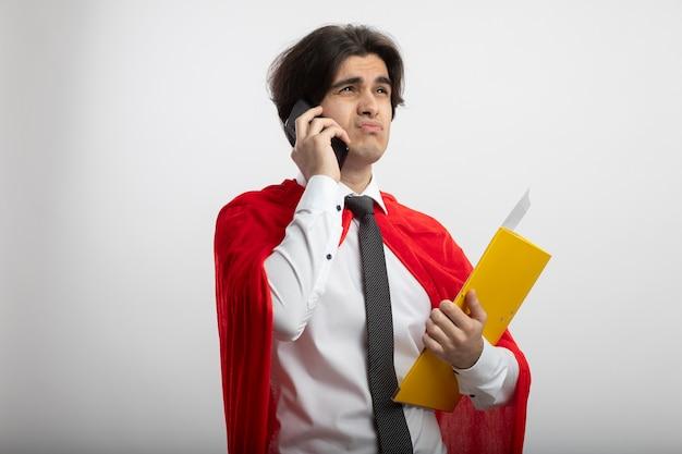 ネクタイ保持フォルダーを身に着けている側を見て不機嫌な若いスーパーヒーローの男は、白で隔離の電話で話します