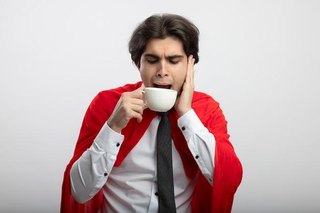 넥타이를 착용하고 불쾌한 젊은 슈퍼 히어로 남자가 컵에서 커피를 마시고 뺨에 손을 댄다.