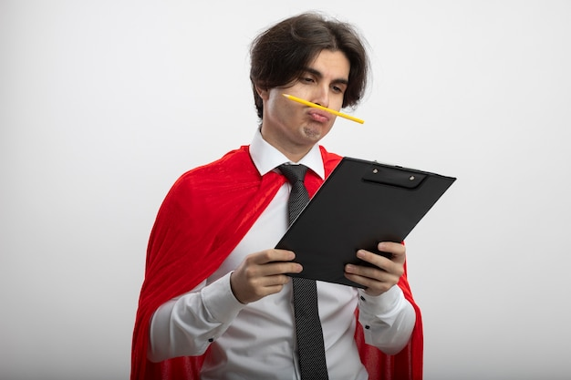Unpleased young superhero guy wearing tie holding and looking at clipboard putting pencil on lips