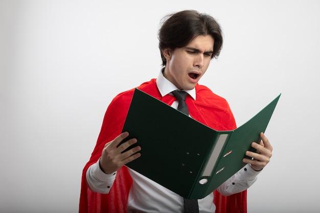 Ragazzo giovane supereroe dispiaciuto che indossa la cravatta che tiene e che esamina cartella isolata su bianco