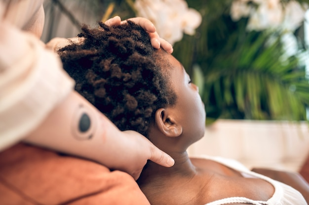 Unplugged. caucasian hands with tattoo touching head and neck of lying dark-skinned woman with short curly hair in spa