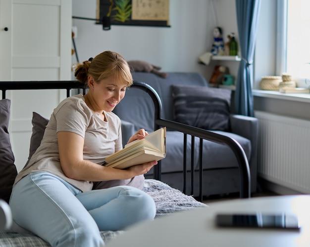 Отключенная улыбающаяся женщина, читающая книгу на диване, бесплатная концепция цифрового детокса на выходных
