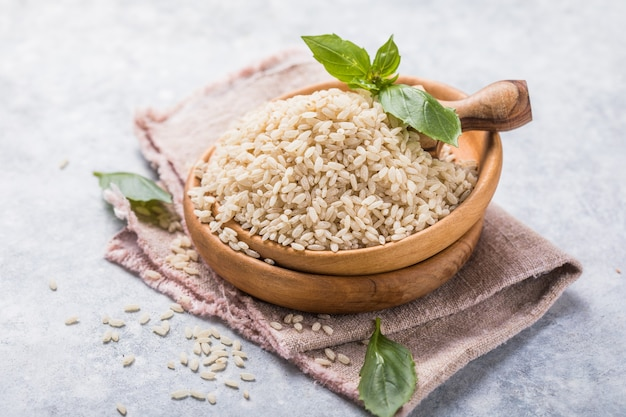 Unpolished brown rice in wooden bowl. long grain rice background.