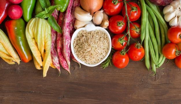 Нешлифованный сырой рис и овощи на деревянной поверхности
