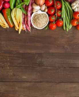 Unpolished raw rice and fresh raw vegetables on brown wooden table top view with copy space