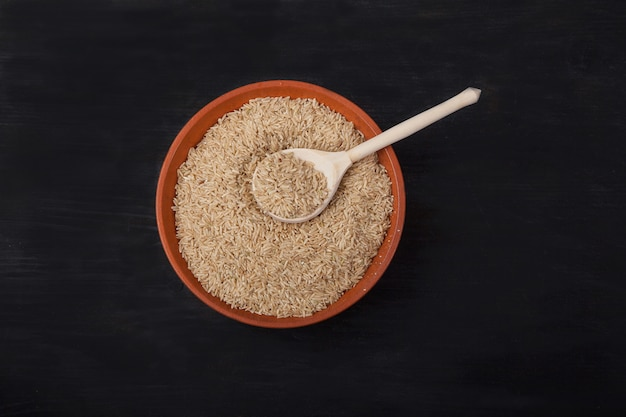 Unpolished rice with a wooden spoon in a clay bowl on a black background