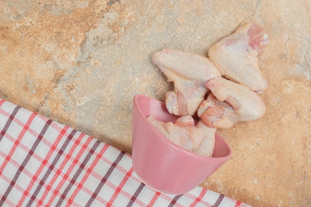 Unprepared chicken legs in pink plate on marble surface