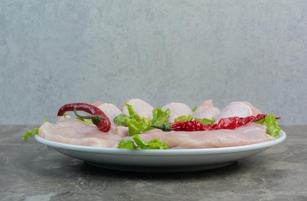 Cosce di pollo non preparate con pepe e lattuga sul piatto bianco. foto di alta qualità