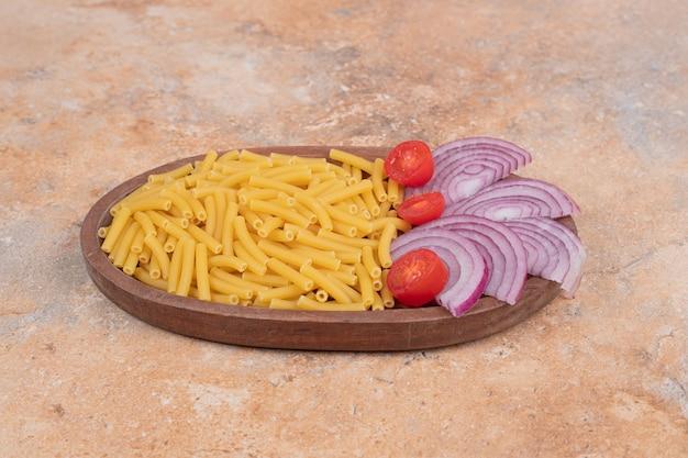 タマネギとトマトチェリーのスライスと準備されていない新鮮なマカロニ。高品質の写真