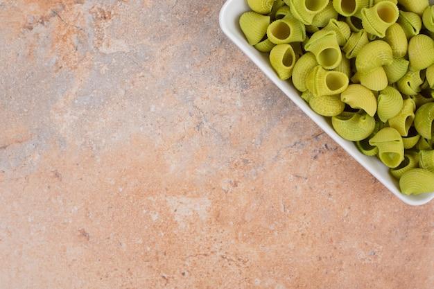 大理石の背景に白いプレートで準備されていない緑のマカロニ。高品質の写真