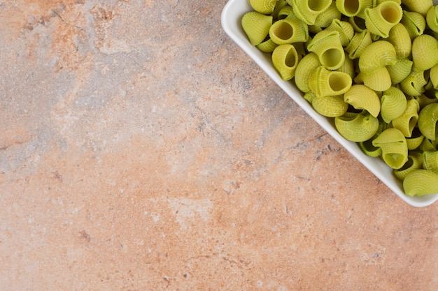 Unprepared green macaroni in white plate on marble background. high quality photo