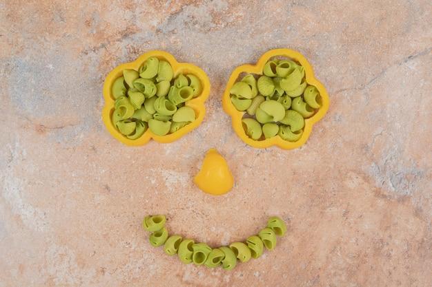 Maccheroni verdi non preparati in peperone giallo sullo spazio di marmo