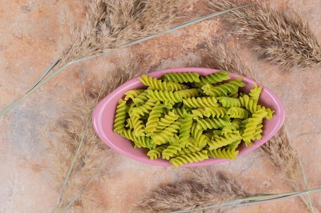 Pasta a spirale verde non preparata sulla ciotola rosa. foto di alta qualità