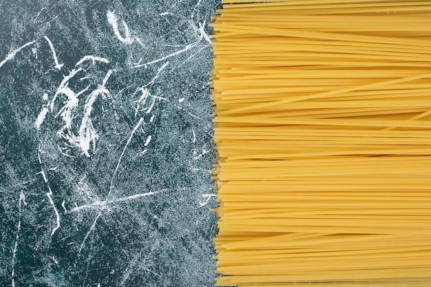 大理石の背景に全粒粉スパゲッティの準備されていないパスタの束