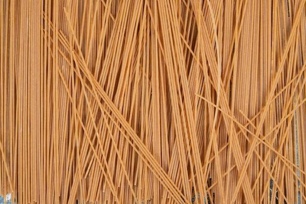 Mazzo di spaghetti integrali di pasta non preparata su spazio di marmo