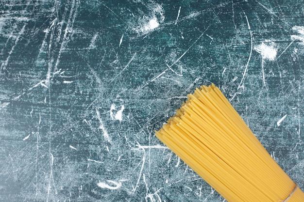 Unprepared pasta mazzetto di spaghetti integrali legati con una corda su marmo backgroundto