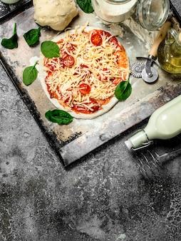 Unprepared pizza with ingredients.