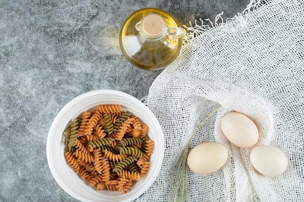 Maccheroni a spirale non preparati in piatto bianco con tre uova e una bottiglia di olio
