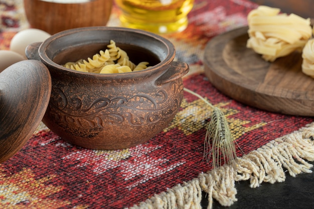 Unprepared spiral pasta in pot with eggs and small wooden bowl of flour